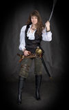 The girl - pirate with a sabre in hands. On a black background Stock Images