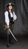 The girl - pirate with a sabre in hands. On a black background Royalty Free Stock Image