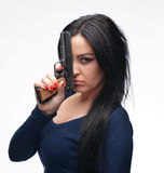 Girl with a pistol. Young girl with a pistol on a white background Stock Photography