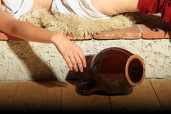Girl with pitcher. Young girl lying on fur with hand near by pitcher lying on floor Royalty Free Stock Images
