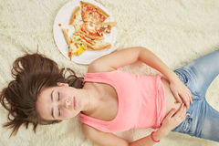 Girl with pizza. Fun sad overeat girl lying with pizza pieces Stock Image
