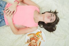 Girl with pizza. Overeat girl with closed eyes lying on bed with pizza Royalty Free Stock Images