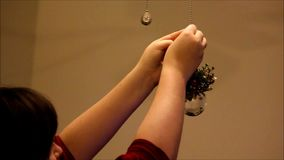 Girl places ornament up to decorate stock footage