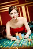 Girl placing a bet at the casino Royalty Free Stock Photos