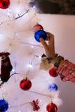 Girl placing Christmas ornaments Royalty Free Stock Photos