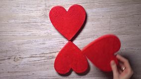 Girl placing four red hearts on a wooden table, top view. Flower, care, love, Valentine's day concepts. 4K video. Girl placing four red hearts on a wooden table stock video footage