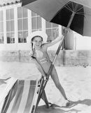 Girl placing a large umbrella into the sand Stock Images