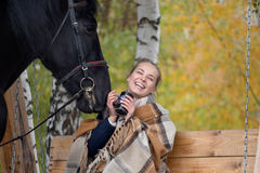 Girl in a plaid with a black horse in the autumn under a birch tree on a bench Stock Photos