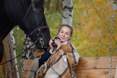Girl in a plaid with a black horse in the autumn under a birch tree on a bench Royalty Free Stock Images