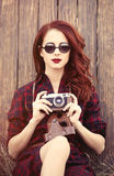 Girl in plaid dress with camera and sunglasses Royalty Free Stock Images