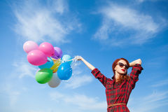 Girl in plaid dress with multicolored balloons Stock Photo