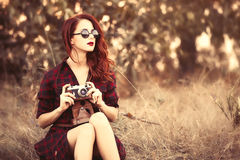 Girl in plaid dress retro camera and sunglasses Royalty Free Stock Photo