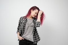 The girl in a plaid gray shirt on a white background with dyed red hair. royalty free stock photography