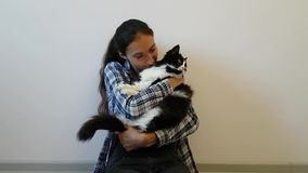 A girl in a plaid shirt hugs her favorite black and white cat. Chubby kitty is not very happy with such tenderness. Funny animal stock video