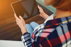 The girl in a plaid shirt and jeans holding a tablet pc Royalty Free Stock Photo