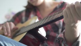 A girl in a plaid shirt learns to play the guitar. Guitar in focus. Playing guitar. Close-up of a woman`s guitar and hands