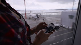 Girl in plaid shirt looks messages from friends, then checks email at the airport against the window in which the. Part of female body in red plaid shirt looks stock footage