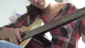 The girl in a plaid shirt plays the guitar. Guitar in focus. The girl is blurred. She touches the strings and clamps them with her fingers