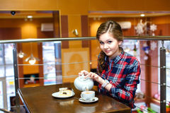 Girl in a plaid shirt pours green tea Royalty Free Stock Images