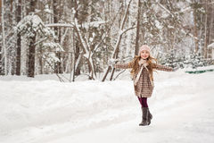 Girl in plaid winter coat happily runs in winter woods Royalty Free Stock Images