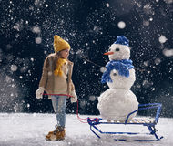 Girl plaing with a snowman Royalty Free Stock Image