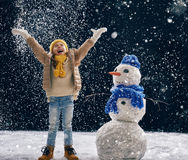Girl plaing with a snowman Royalty Free Stock Photo