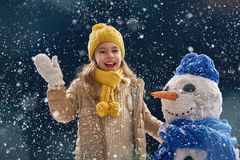 Girl plaing with a snowman Royalty Free Stock Photography