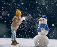 Girl plaing with a snowman Royalty Free Stock Photos