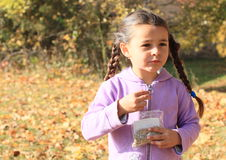 Girl with plaits eating seeds Royalty Free Stock Photography