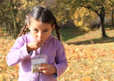 Girl with plaits eating seeds Royalty Free Stock Photos