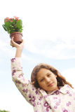 Girl with plant pot against blue sky. Stock Image