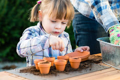 Free Girl Planting Flower Seeds Into Pots With Her Mother Royalty Free Stock Photo - 59121275