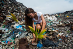 Girl planting tree among trash at garbage dump Royalty Free Stock Photos
