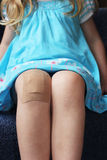 Girl with plaster on her knee Royalty Free Stock Images