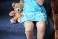 Girl with plaster on knee cuddling teddy Stock Image