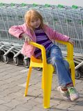 Girl on a plastic chair Royalty Free Stock Image