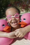 Girl With Plastic Ducks Relaxing On The Edge Of Pool Royalty Free Stock Image