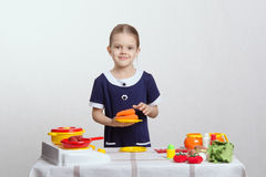 Girl with a plate of carrots on toy kitchen Stock Image
