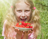 Girl with a plate of strawberries Stock Photos