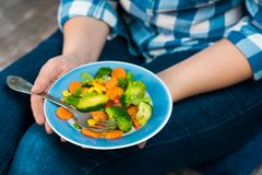 Girl with a plate of vegetables in hands. Healthy eating concept. A girl in jeans and a plaid shirt. Casual Style. Proper nutrition. Diet. Health. Vegetarian Royalty Free Stock Photos