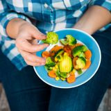 Girl with a plate of vegetables in hands. Healthy eating concept. A girl in jeans and a plaid shirt. Casual Style. Proper nutrition. Diet. Health. Vegetarian Royalty Free Stock Photography