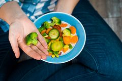 Girl with a plate of vegetables in hands. Healthy eating concept. A girl in jeans and a plaid shirt. Casual Style. Proper nutrition. Diet. Health. Vegetarian Stock Photos