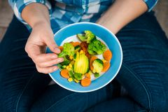 Girl with a plate of vegetables in hands. Healthy eating concept. A girl in jeans and a plaid shirt. Casual Style. Proper nutrition. Diet. Health. Vegetarian Stock Photography