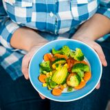 Girl with a plate of vegetables in hands. Healthy eating concept. A girl in jeans and a plaid shirt. Casual Style. Proper nutrition. Diet. Health. Vegetarian Stock Image