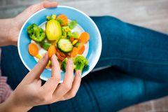 Girl with a plate of vegetables in hands. Healthy eating concept. Girl in jeans and a red shirt in a cage. Casual Style. Proper nutrition. Diet. Health Stock Photos