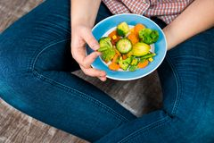 Girl with a plate of vegetables in hands. Healthy eating concept. Girl in jeans and a red shirt in a cage. Casual Style. Proper nutrition. Diet. Health Stock Photo