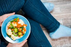 Girl with a plate of vegetables in hands. Healthy eating concept. Girl in jeans and a red shirt in a cage. Casual Style. Proper nutrition. Diet. Health Royalty Free Stock Images