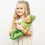 Girl play with baby doll. Mothers day concept. Royalty Free Stock Image