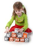 Girl play with bricks. Little girl build the pyramid of letter bricks Royalty Free Stock Images