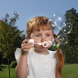 Girl play in  bubbles Stock Images